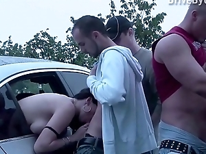 A girl is joining a public sex dogging orgy with several strangers in progress